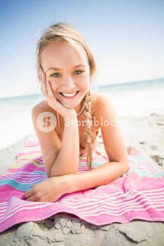 Portrait of happy woman lying on the beach