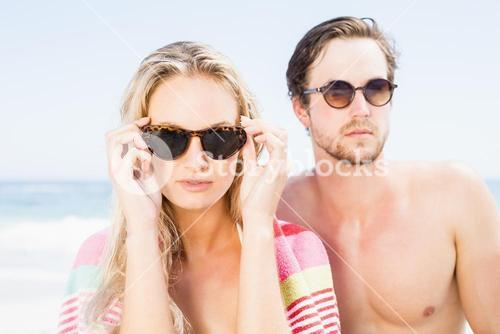 Young couple wearing sunglasses at beach