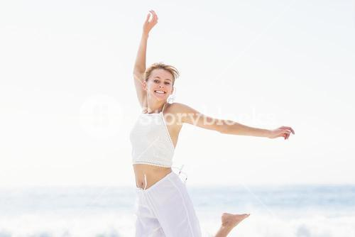 Carefree woman in jumping on the beach