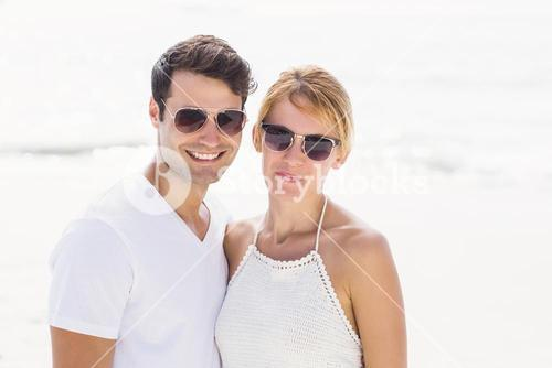 Portrait of young couple in sunglasses at beach