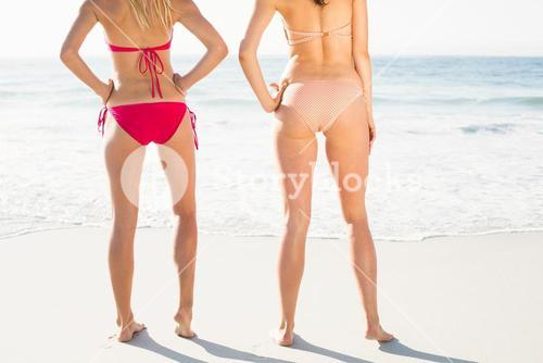 Mid-section of women standing in bikini on the beach
