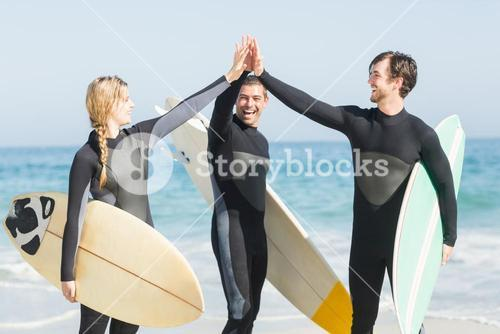 Happy surfer giving high-five to each other on the beach