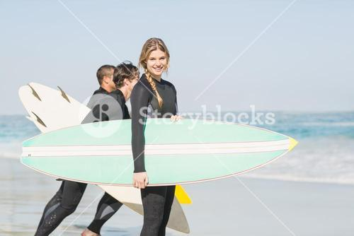 Portrait of surfer woman with surfboard standing on the beach
