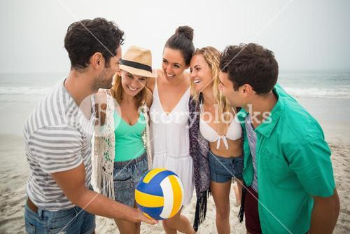 Group of friends with beach ball having fun on the beach