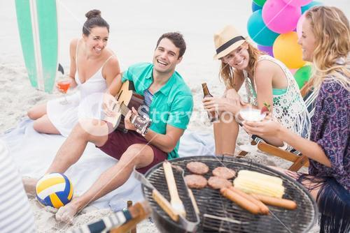 Group of friends with drinks and guitar sitting next to a barbecue