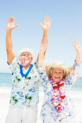 Senior couple with arms up on the beach