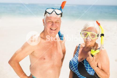 Senior couple wearing snorkel and diving goggles