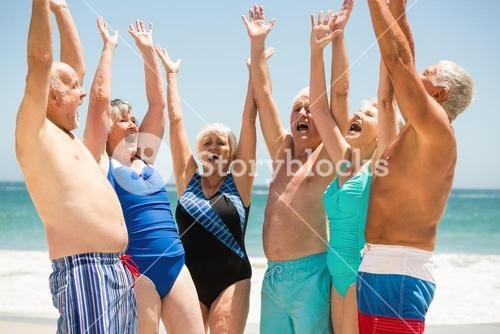 Seniors with hands up at the beach