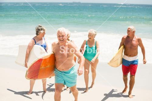 Seniors carrying surfboards at the beach
