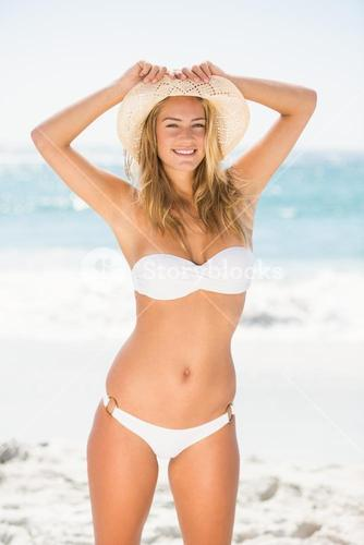 Smiling woman standing at the beach