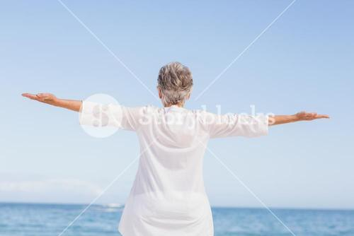 Casual senior woman with arms outstretched