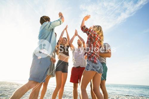 Friends doing high five on the beach