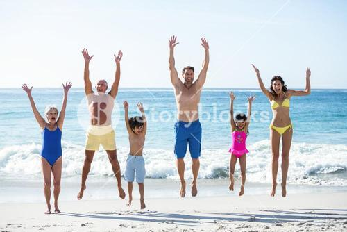 Happy family jumping on the beach