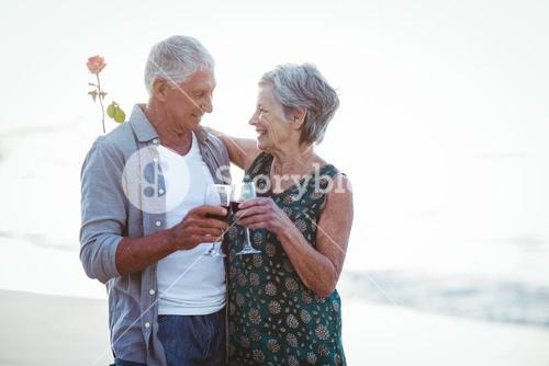 Senior couple holding rose and red wine glasses