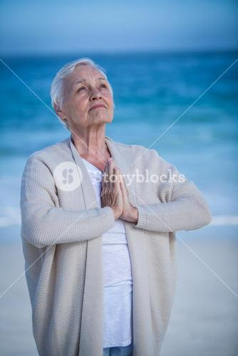 Senior woman relaxing with joined hands