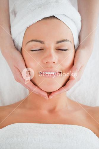 Portrait of a smiling woman having a facial massage