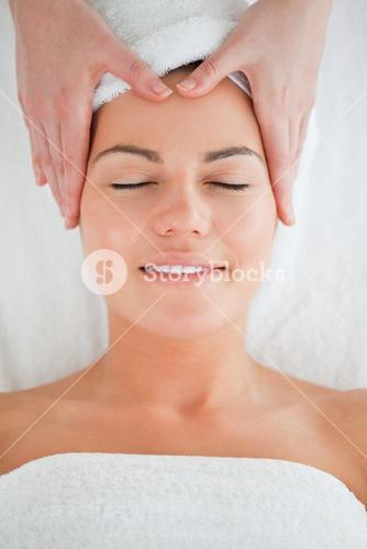 Portrait of a happy woman enjoying a facial massage