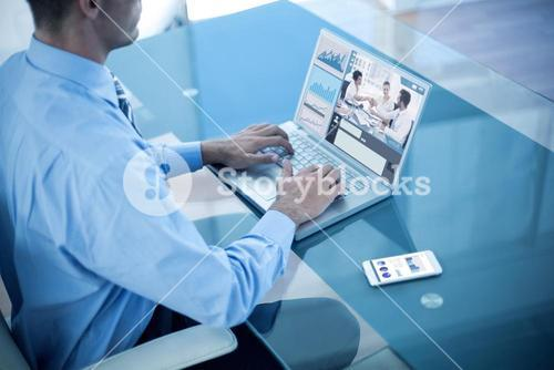 Composite image of businessman using his laptop