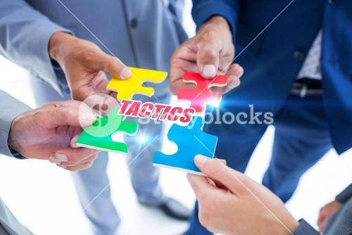 Tactics against business colleagues holding piece of puzzle