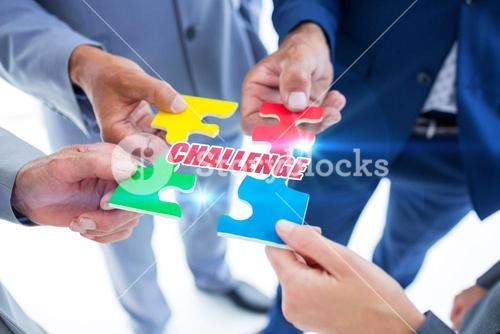 Challenge against business colleagues holding piece of puzzle