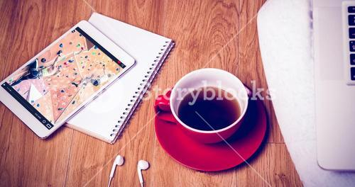 Composite image of overhead shot of laptop, tablet, coffee and headphones