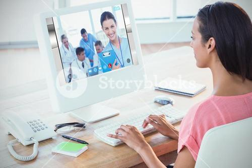 Composite image of businesswoman using computer at desk in creative office