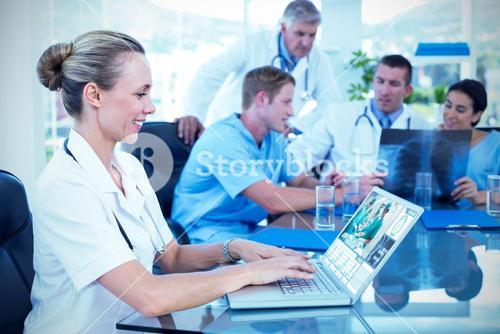Composite image of beautiful smiling doctor typing on keyboard with her team behind