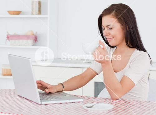 Darkhaired woman using her laptop and having a tea