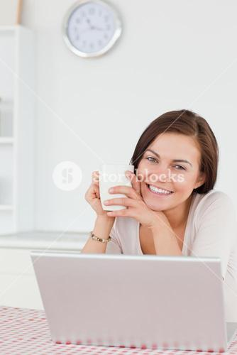 Smiling darkhaired woman using her laptop and having a tea
