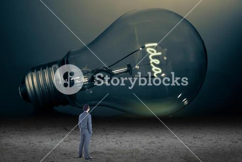Businessman looking at giant light bulb