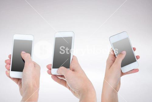Three hands holding smartphones
