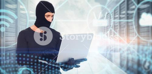 Composite image of burglar with balaclava hacking a laptop