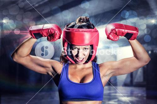 Composite image of portrait of angry female boxer flexing muscles