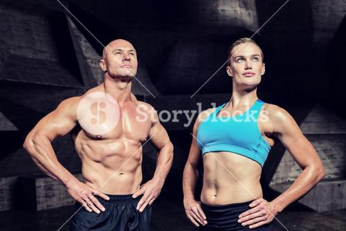 Composite image of muscular man and woman with hand on hip