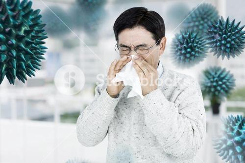 Composite image of smiling man using a tissue