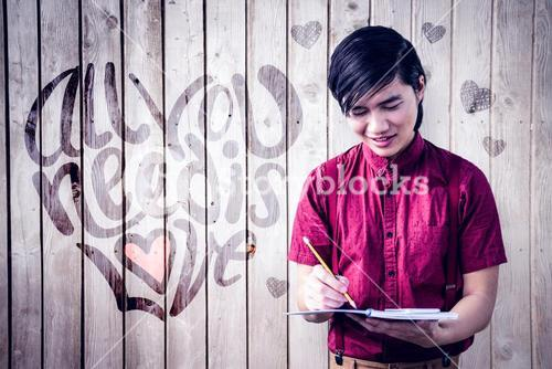 Composite image of smiling hipster takes notes with his smartphone