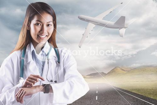 Composite image of asian doctor using her smart watch