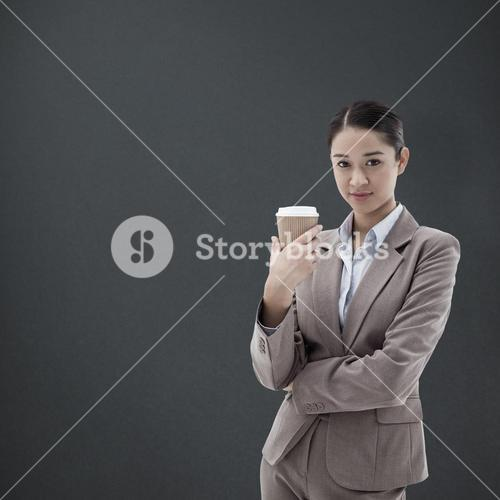 Composite image of portrait of a businesswoman holding a takeaway tea