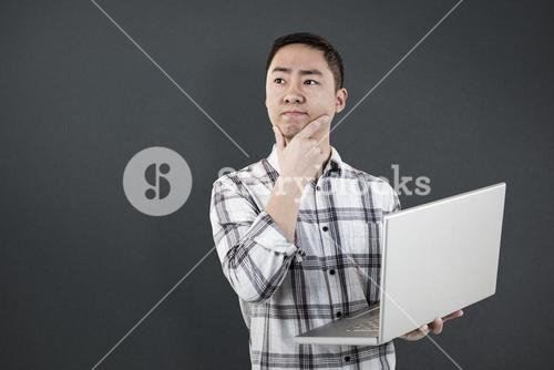Composite image of thoughtful man holding laptop