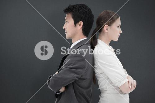 Composite image of portrait of serious business people standing back-to-back