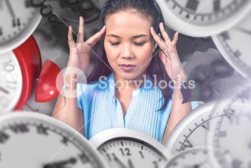 Composite image of worried businesswoman holding her head