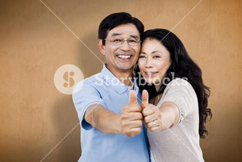 Composite image of smiling couple with thumbs up