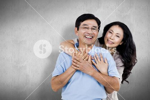 Composite image of smiling couple holding each other