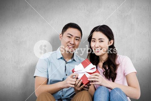 Composite image of happy couple holding gift box
