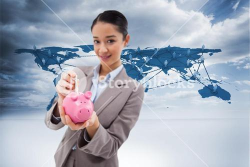 Composite image of portrait of a businesswoman putting a bank note in a piggy bank