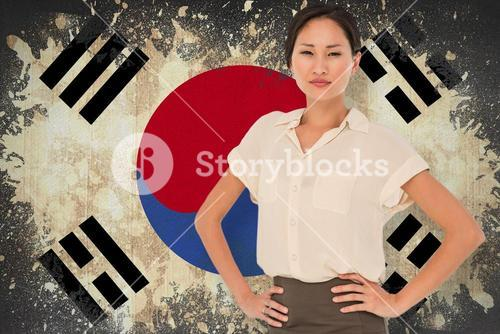 Composite image of asian businesswoman with hands on hips