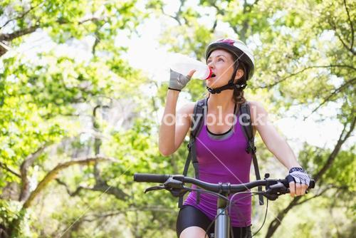 Woman drinking water while cycling