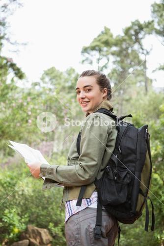 Smiling woman with backpack and map