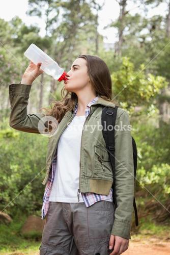 Woman drinking water with backpack
