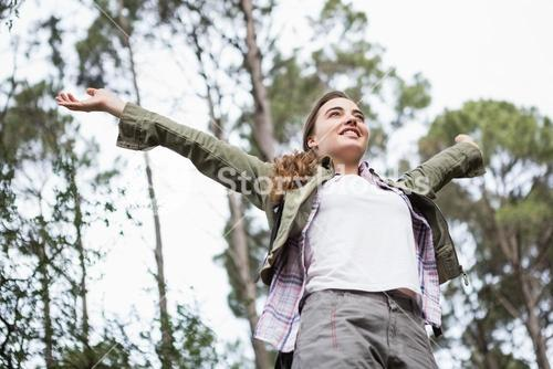 Smiling woman with arms up